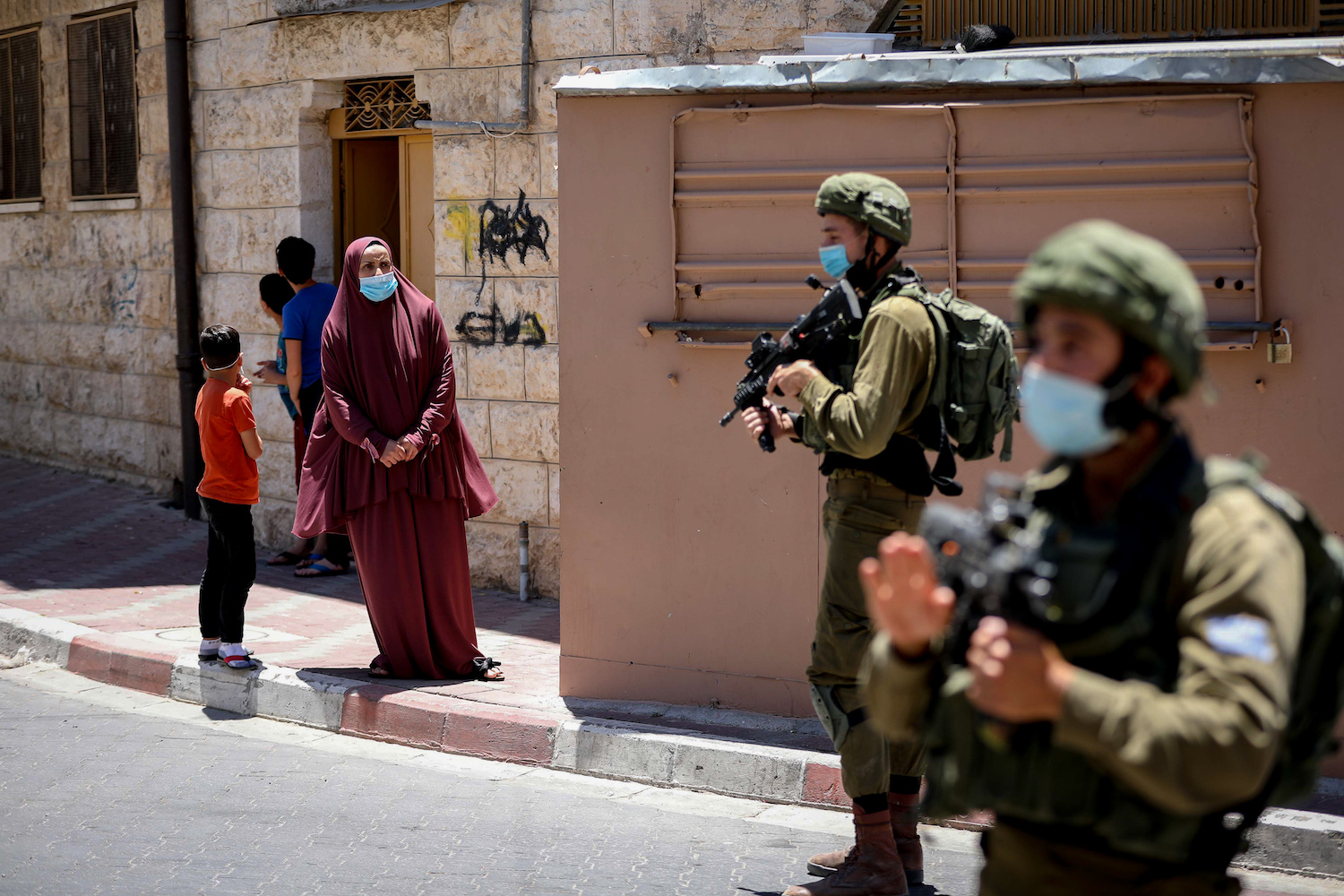 Israeli soldiers stand at checkpoint in the West Bank city of Hebron, June 25, 2020. (Wisam Hashlamoun/Flash90)