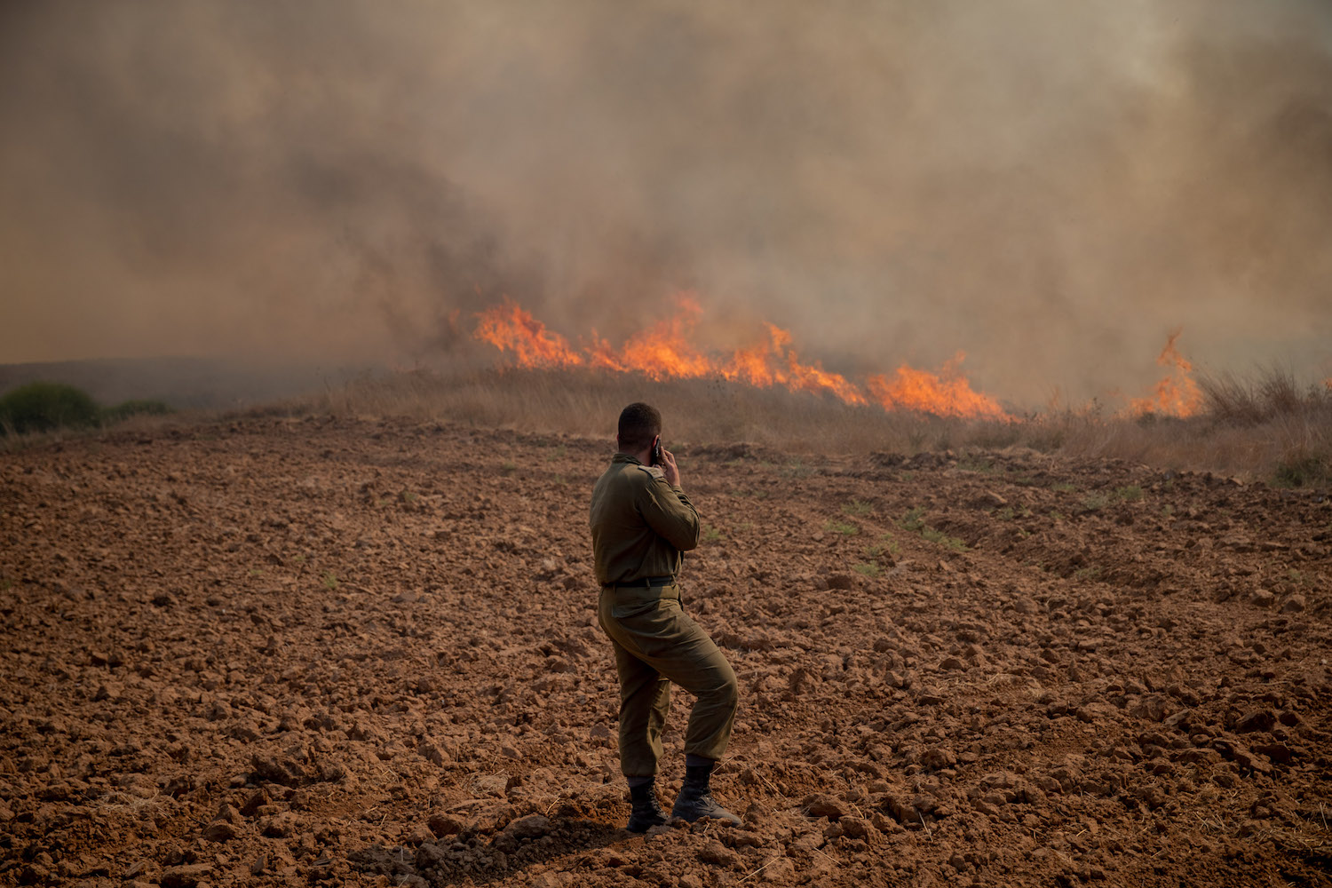 An Israeli soldier gazes at a fire near Kibbutz Be'eri, caused from incendiary kites launched by Palestinians from the Gaza Strip, August 13, 2020. (Yonatan Sindel/Flash90)