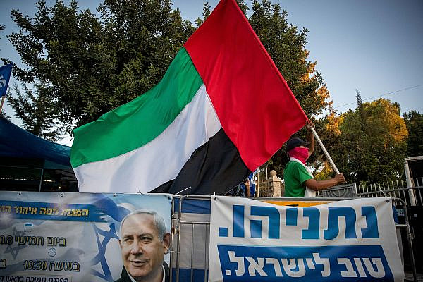 A man waves a United Arab Emirates flag outside the Israeli Prime Minister's official residence in Jerusalem, August 19, 2020. (Yonatan Sindel/Flash90)