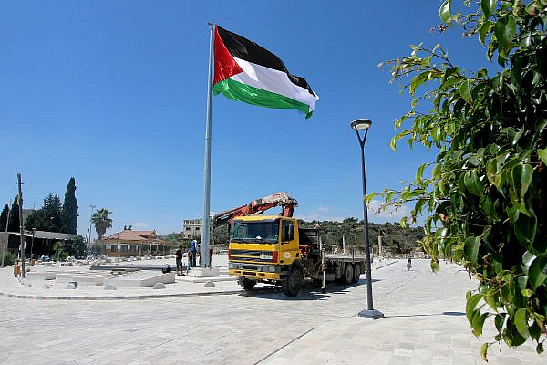 Palestinian workers working on the newly-installed flagpole at the public plaza of the town of Sebastia, West Bank, August 24, 2020. (Ahmad al-Bazz/Activestills)