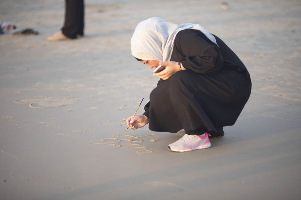 A young Palestinian woman writes in the sand on the beaches of Jaffa. (Oren Ziv/Activestills)