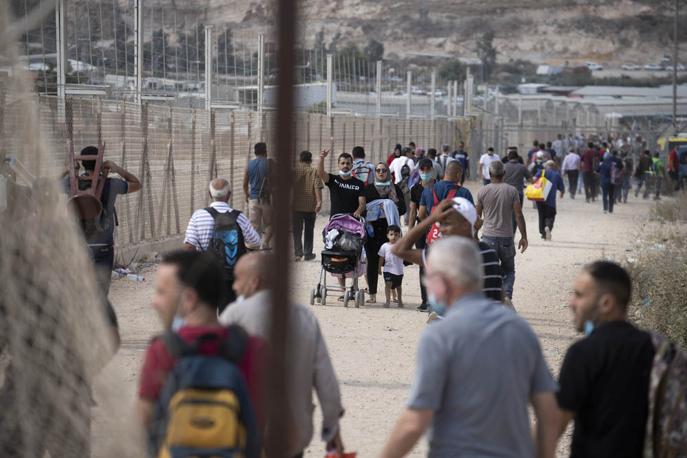 Palestinians walking through a hole in the Israeli separation barrier next to the West Bank village of Far'oun near Tulkarem. (Activestills)