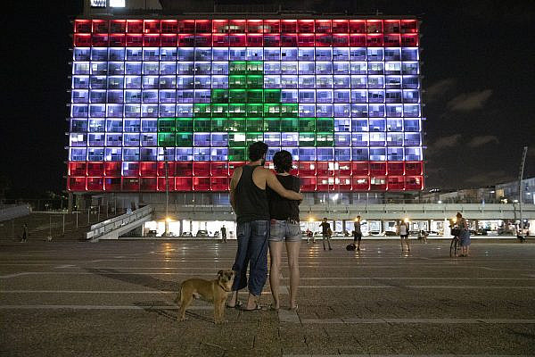 An Israeli couple watches as the Tel Aviv City Hall lights up in the color of the Lebanese flag, following a devastating explosion at the port of Beirut, August 5, 2020. (Orly Noy)