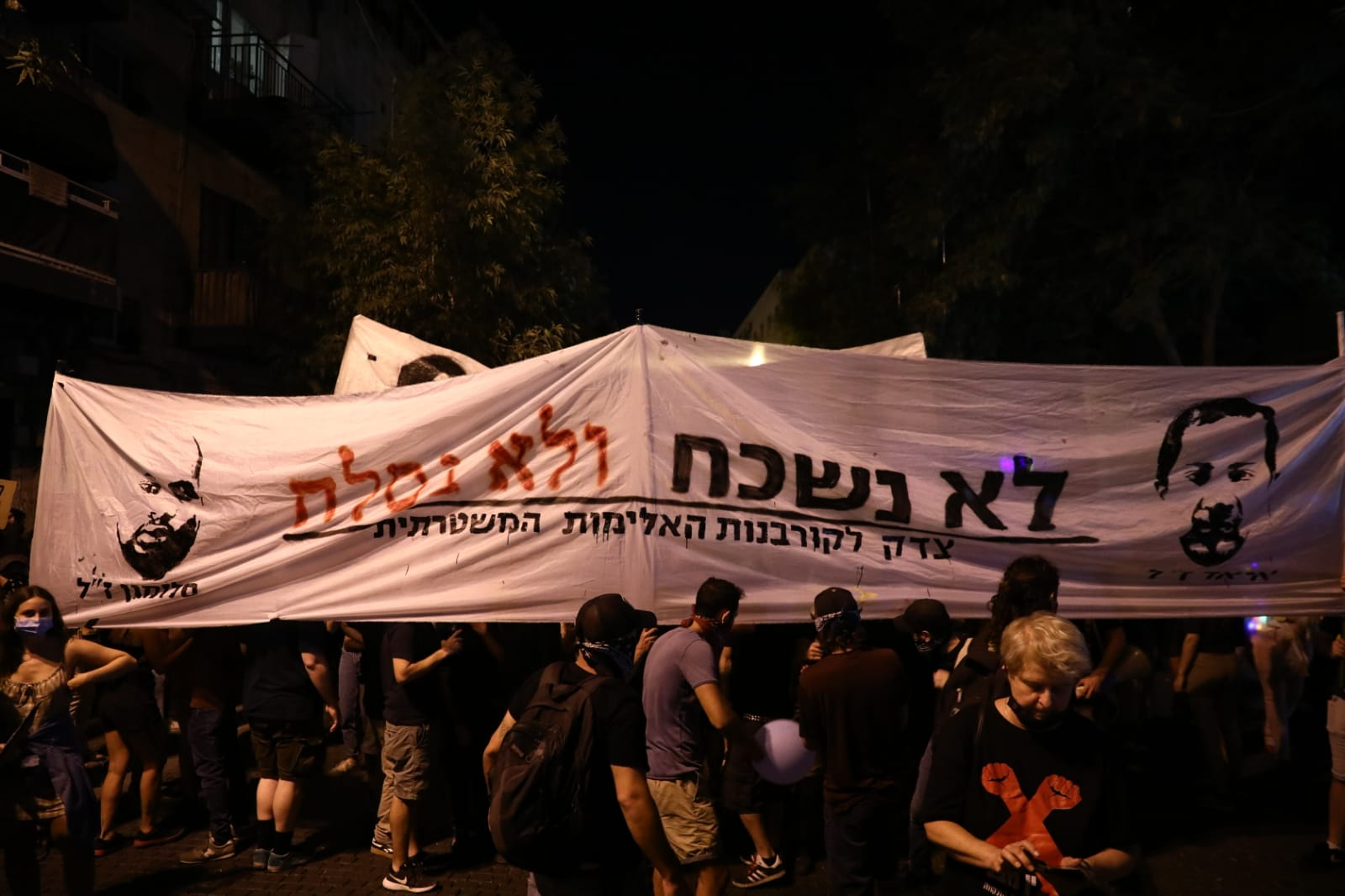 Protesters carry a sign demanding justice for the police killings of Palestinian Iyad al-Hallaq and Ethiopian Israeli Solomon Tekah during an anti-Netanyahu demonstration in Jerusalem, August 1, 2020. (Oren Ziv/Activestills)
