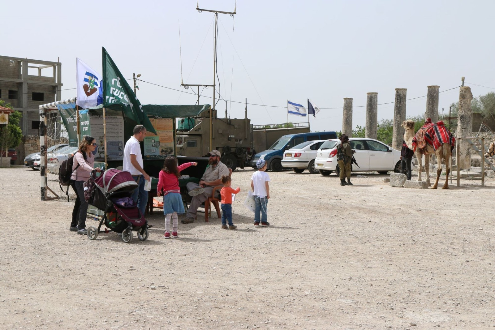 Israeli settlers visit the public plaza of Sebastia, West Bank, escorted by the Israeli army on a Jewish holiday, April 12, 2017. (Ahmad al-Bazz/Activestills)