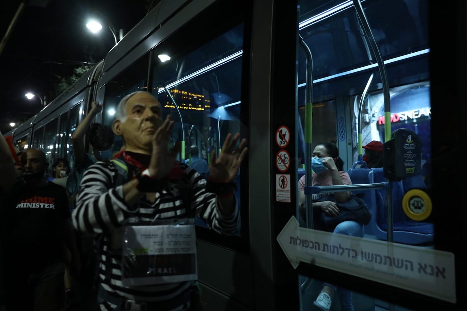 A demonstrator dressed up as Netanyahu in prisoner clothing seen standing alongside the Jerusalem Light Rail during anti-Netanyahu protests in the city, August 29, 2020. (Oren Ziv)
