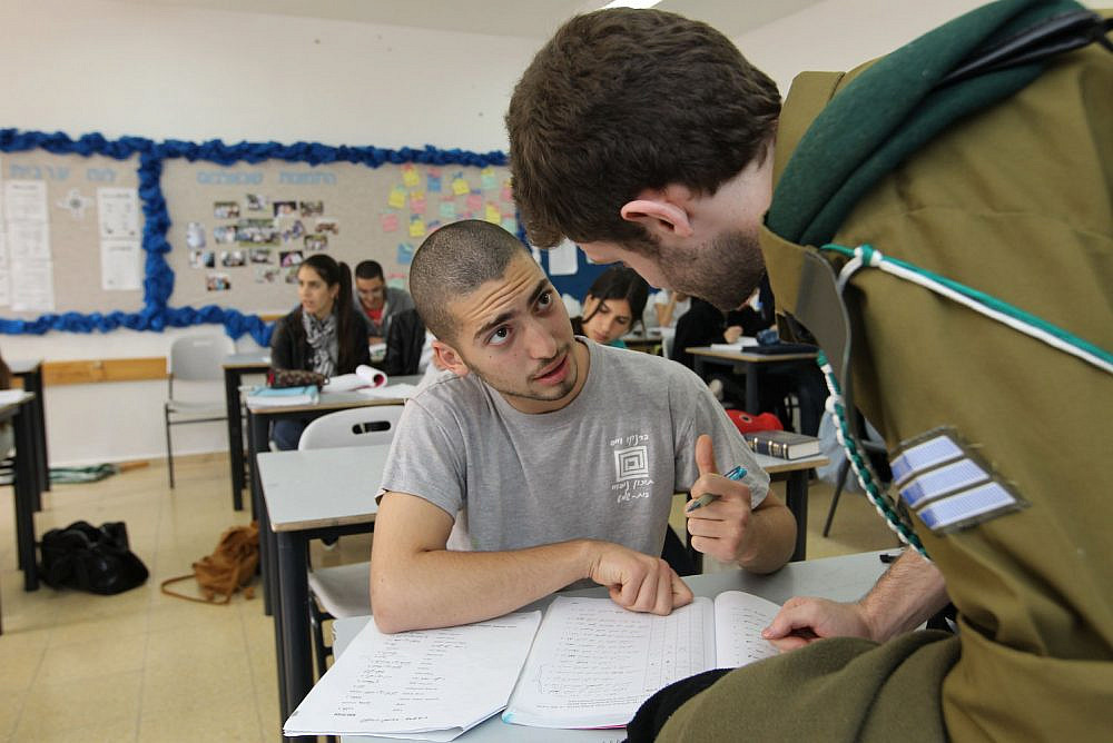 A teacher-soldier speaks to a student in a classroom in Beit Shemesh, April 4 2011. (Nati Shohat/Flash90)