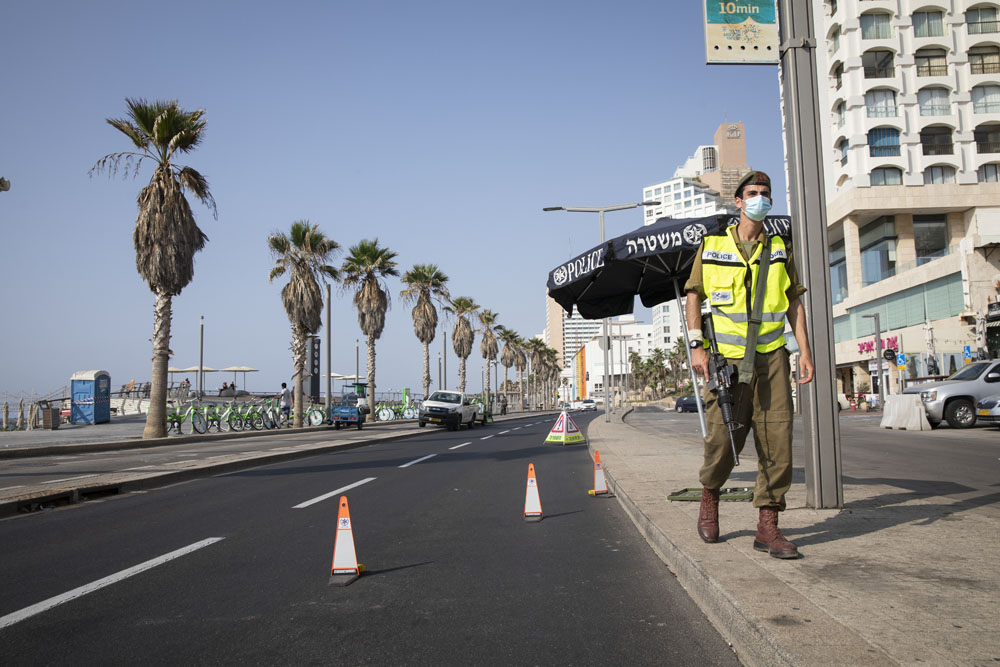 An Israeli soldier stands by a makeshift checkpoint near the Tel Aviv promenade after the government imposed a nationwide lockdown, September 18, 2020. (Oren Ziv)