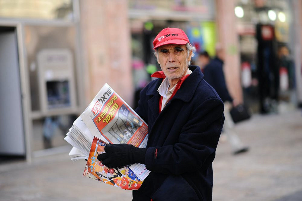A man passes out the free daily newspaper Israel HaYom to passersby on Ben Yehuda Street in Jerusalem on February 6, 2015. (Mendy Hechtman/Flash90)