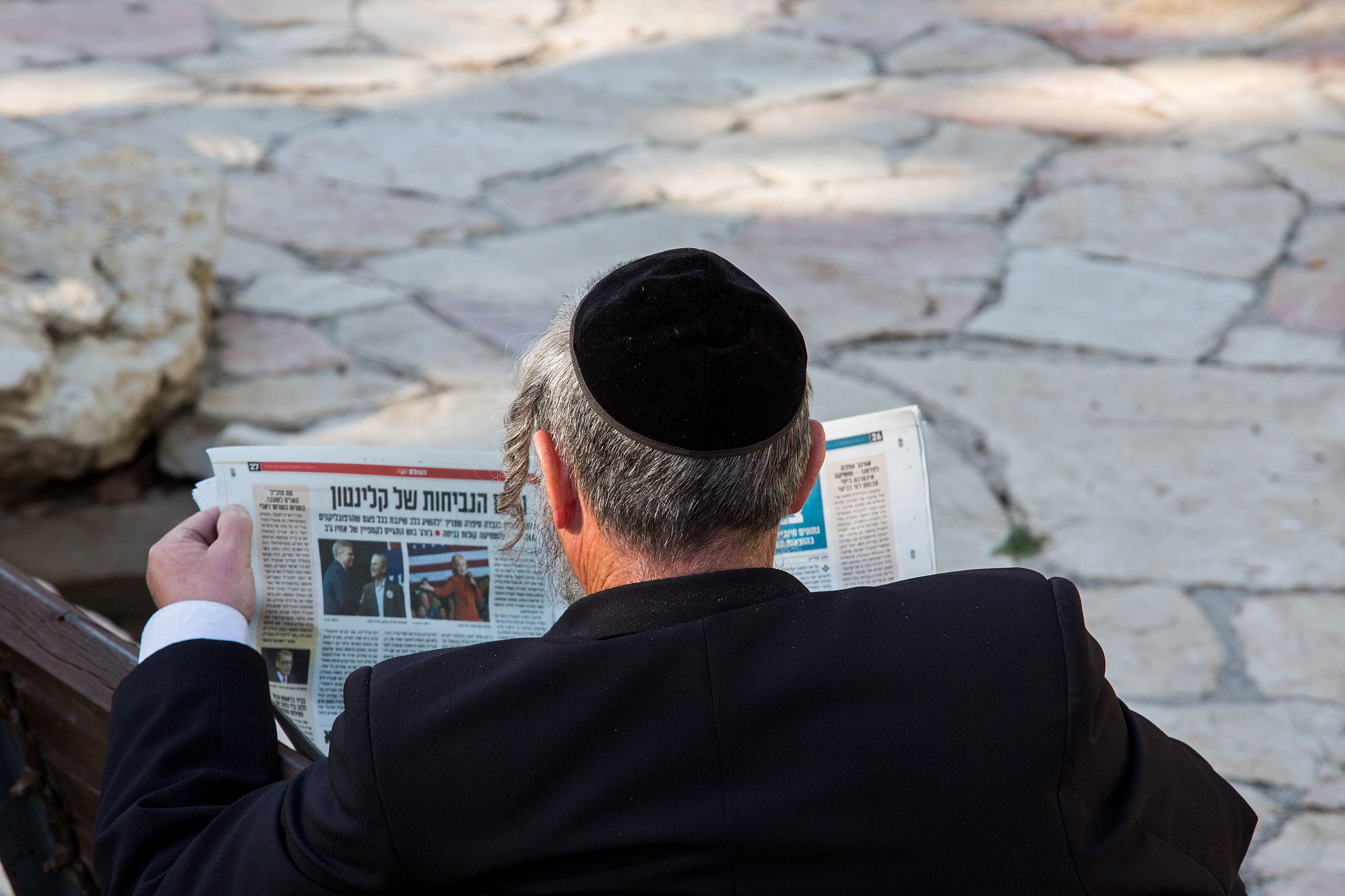 An ultra-Orthodox Jewish man reads the Israel Hayom newspaper in Jerusalem, February 17, 2016. (Nati Shohat/Flash90)