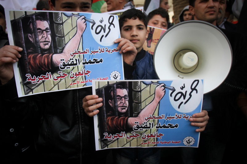 Palestinians hold posters of journalist and former hunger striking prisoner Mohammed al-Qiq during a protest in support of Ahmed Nassar who was jailed in Israeli prison, in the West Bank city of Nablus, March 07, 2017. (Nasser Ishtayeh/Flash90)