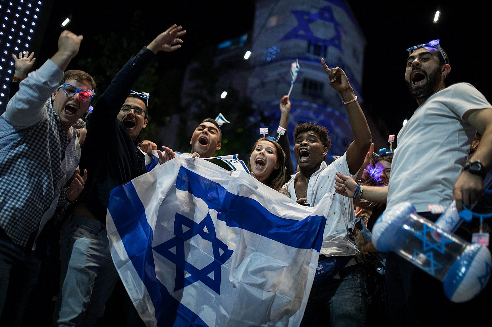 People wear Israeli flags as they take part in celebrations marking Israel's 71st Independence Day in Jerusalem, May 8, 2019. (Hadas Parush/Flash90)