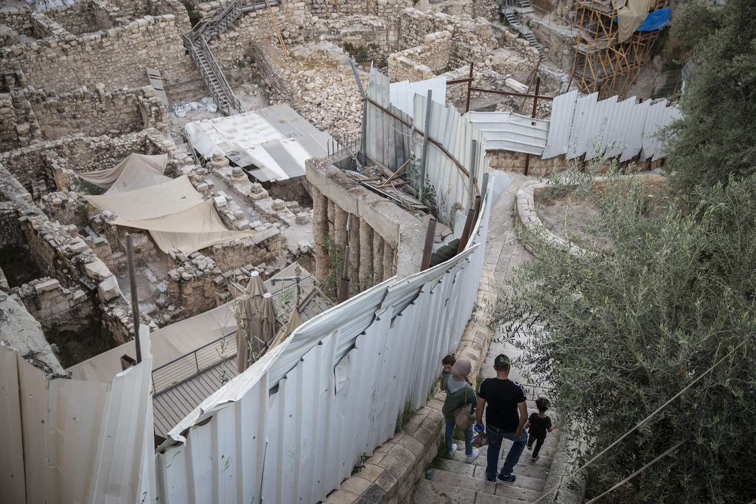 Palestinian residents walk down the stairs next to a fence surrounding the Givati parking lot excavation grounds, as they enter the Palestinian neighborhood of Silwan in occupied East Jerusalem, near the City of David National Park, July 14, 2019. (Hadas Parush/Flash90)
