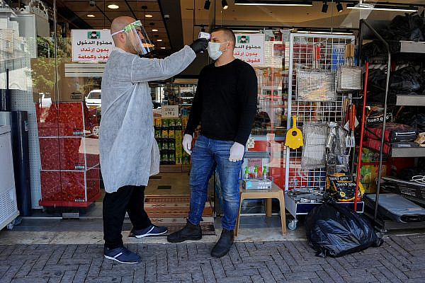A man checks the temperature of a customer to identify if he has a fever, in the northern Arab town of Deir al-Asad, April 18, 2020. (Basel Awidat/Flash90)
