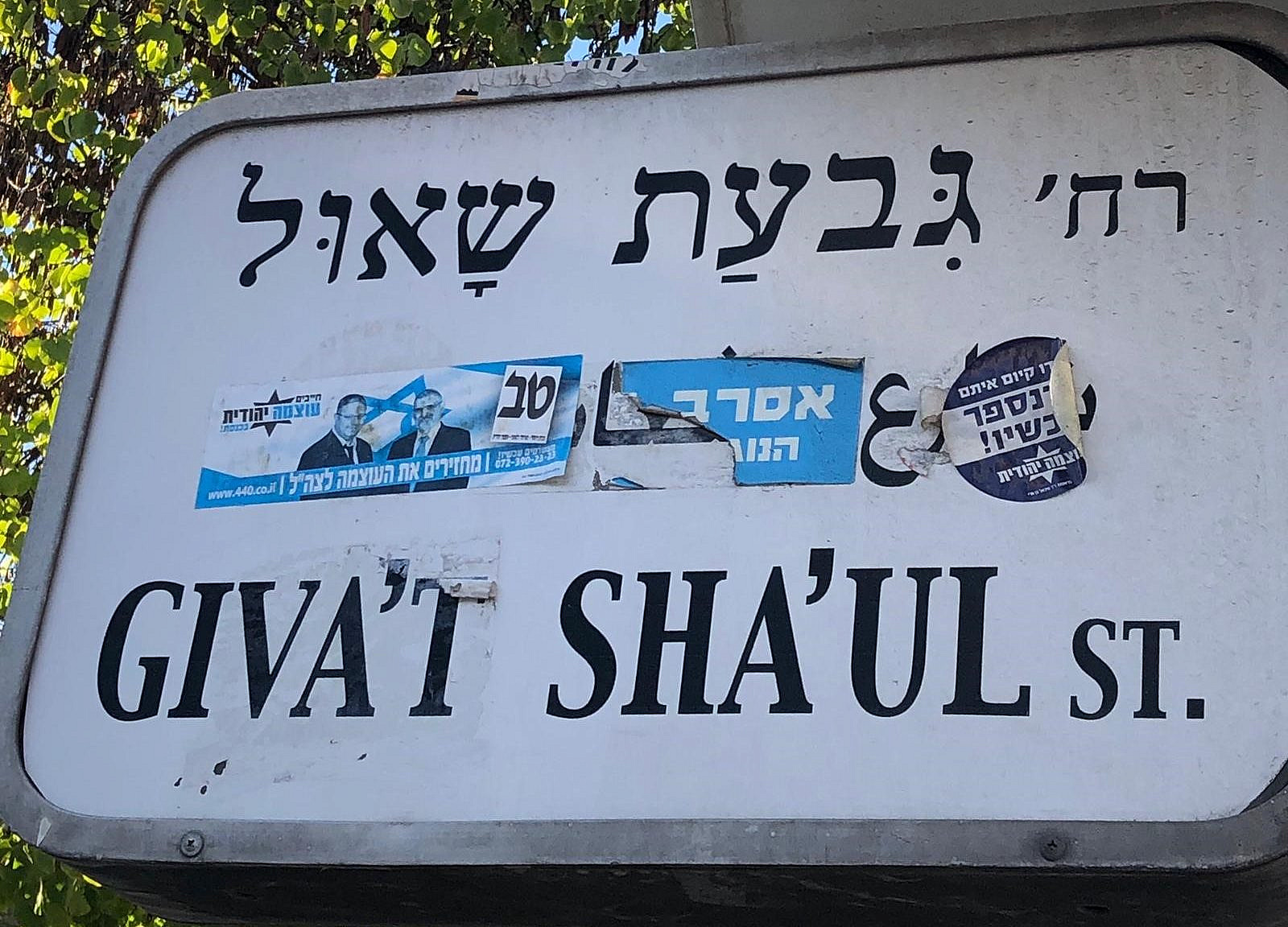 Three different stickers, two of them for the Otzma Yehudit party, covering the Arabic on a street sign in the Givat Sha'ul neighborhood in Jerusalem. (Ben Reiff)