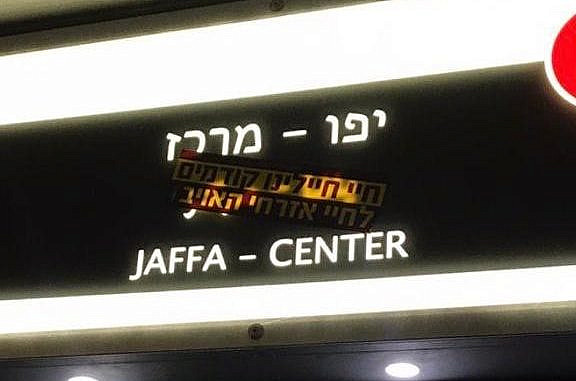 """A sticker reading """"The lives of our soldiers precede the lives of enemy civilians,"""" likely from the Hardali movement Derech Haim, covering the Arabic on a sign at a light rail station in the Jerusalem city center. (Ben Reiff)"""