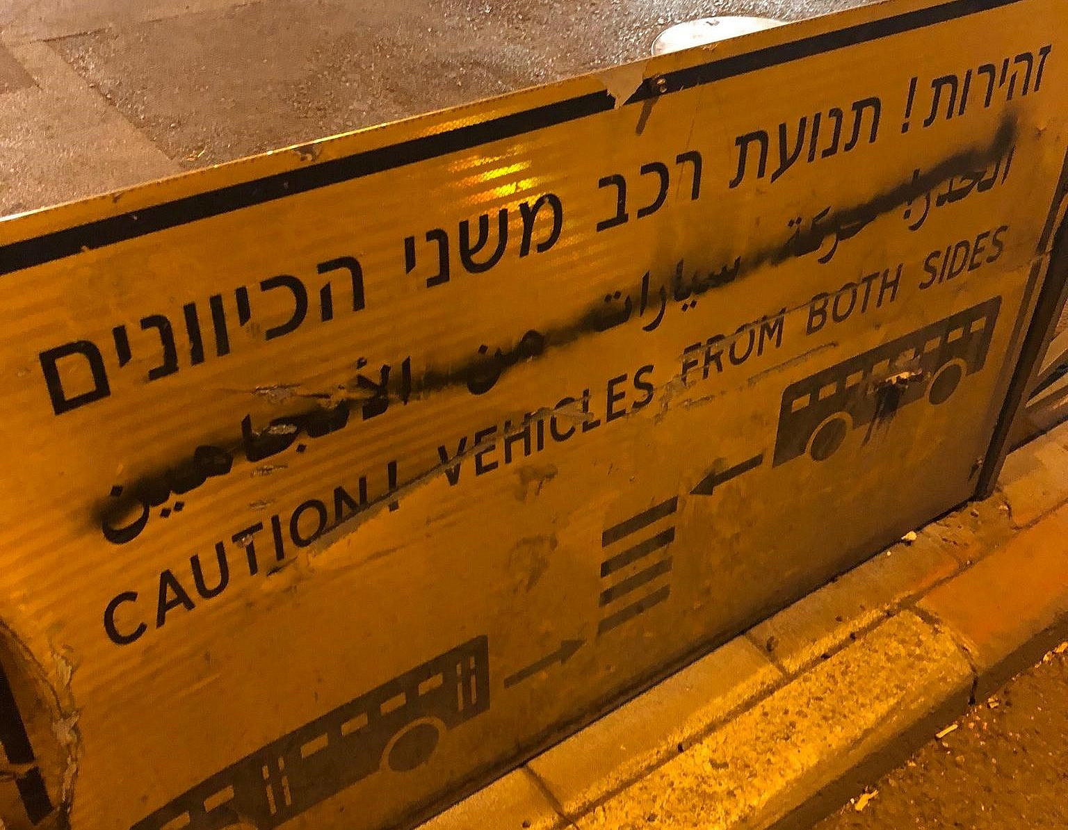 Arabic has been covered by black spray paint on a sign at a pedestrian crossing in Me'ah She'arim, Jerusalem. (Ben Reiff)