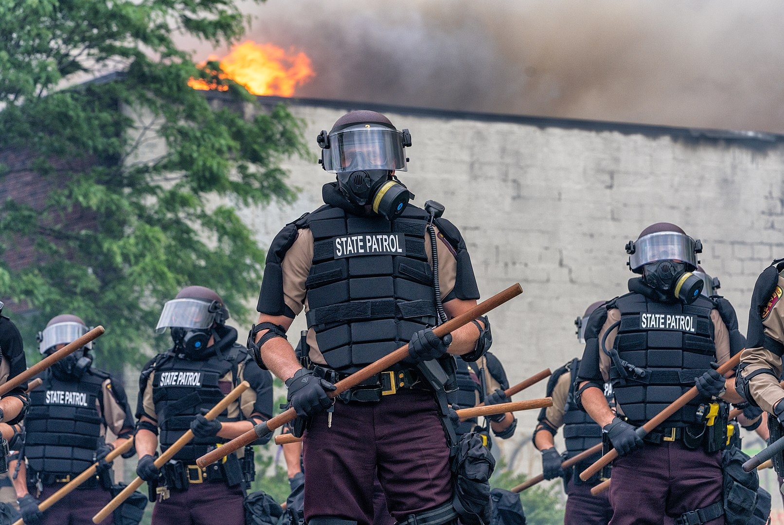 Minnesota State patrol troopers stand in formation, wearing riot gear and holding wooden batons during protests following the killing of George Floyd in Minneapolis, May 29, 2020. (Tony Webster/Flickr)