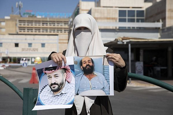 Taghrid al-Akhras, wife of Palestinian administrative detainee Maher al-Akhras, holds up photographs of her husband outside Kaplan Medical Center in Rehovot, where he is on day 73 of a hunger strike. (Oren Ziv/Activestills)