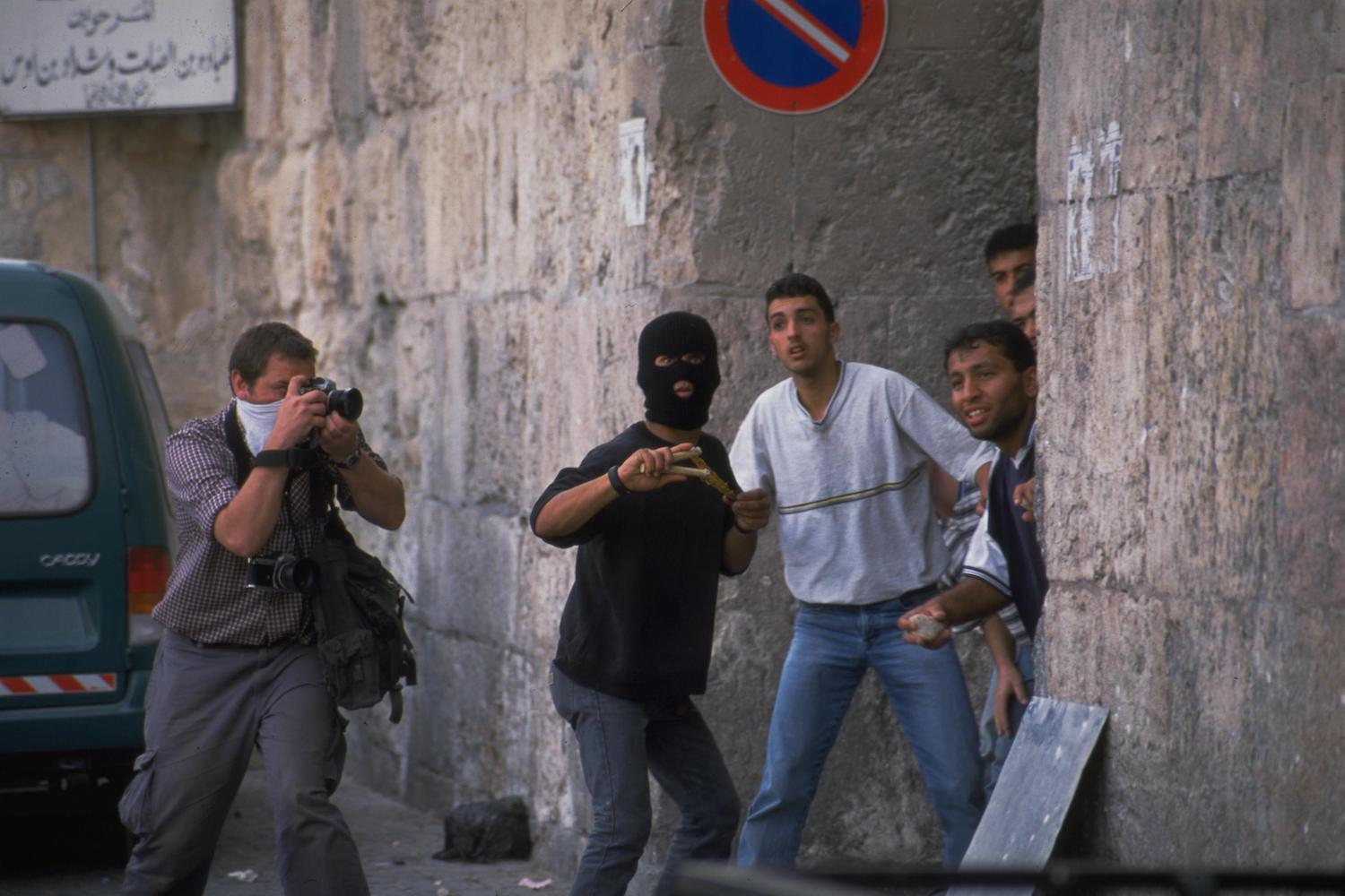 A photographer takes photos of Palestinian protesters during the Second Intifada, near Lions' Gate in Jerusalem, October 6, 2020. (Oded Baliti/GPO)
