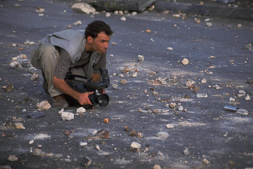 A TV journalist covering protests in the occupied West Bank during the Second Intifada, October 8, 2000. (Oded Baliti/GPO)