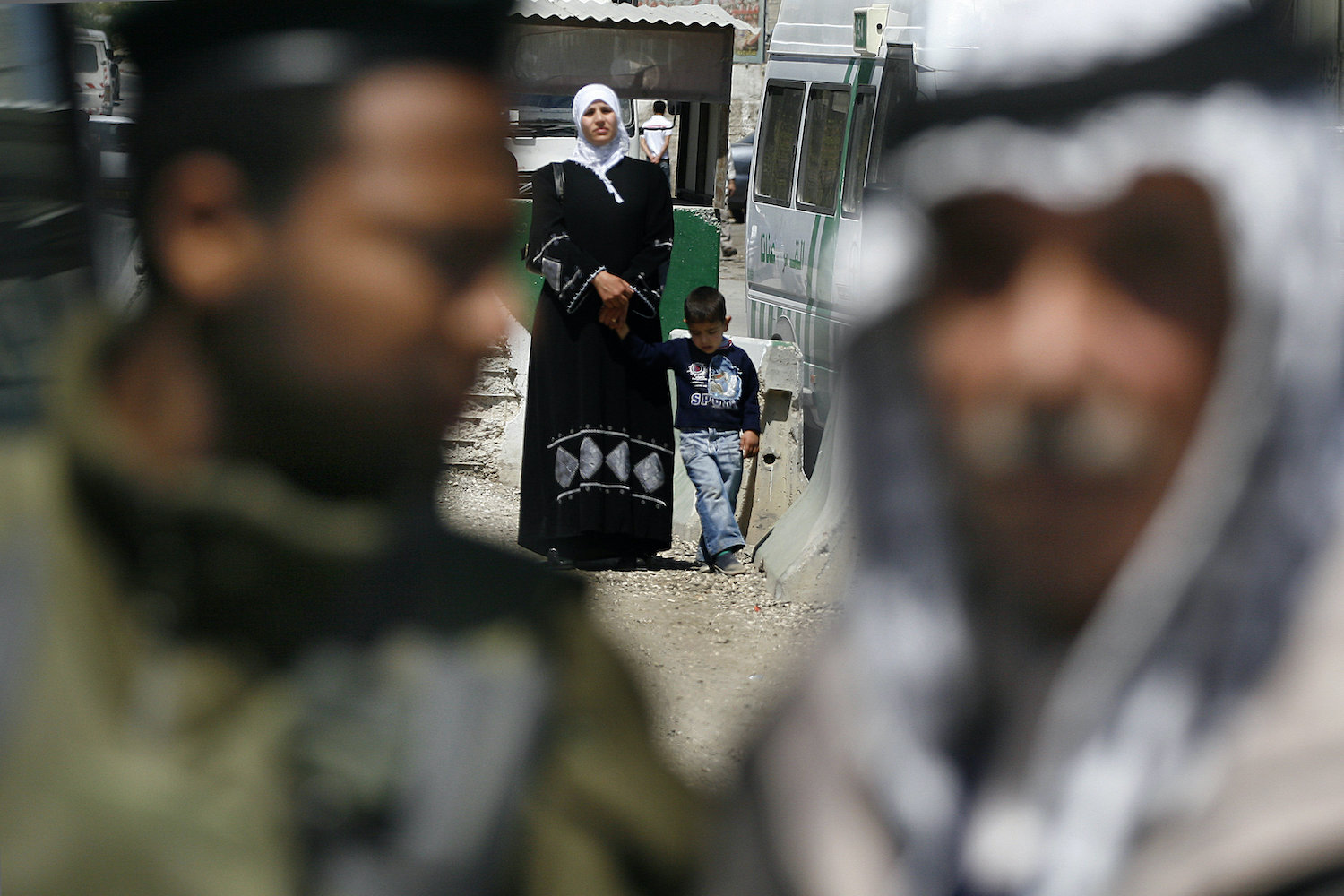A Palestinian mother and son wait to cross the Shu'fat checkpoint into Jerusalem, while an Israeli border policeman checks a Palestinian man, April 20, 2007. (Michal Fattal/Flash90)
