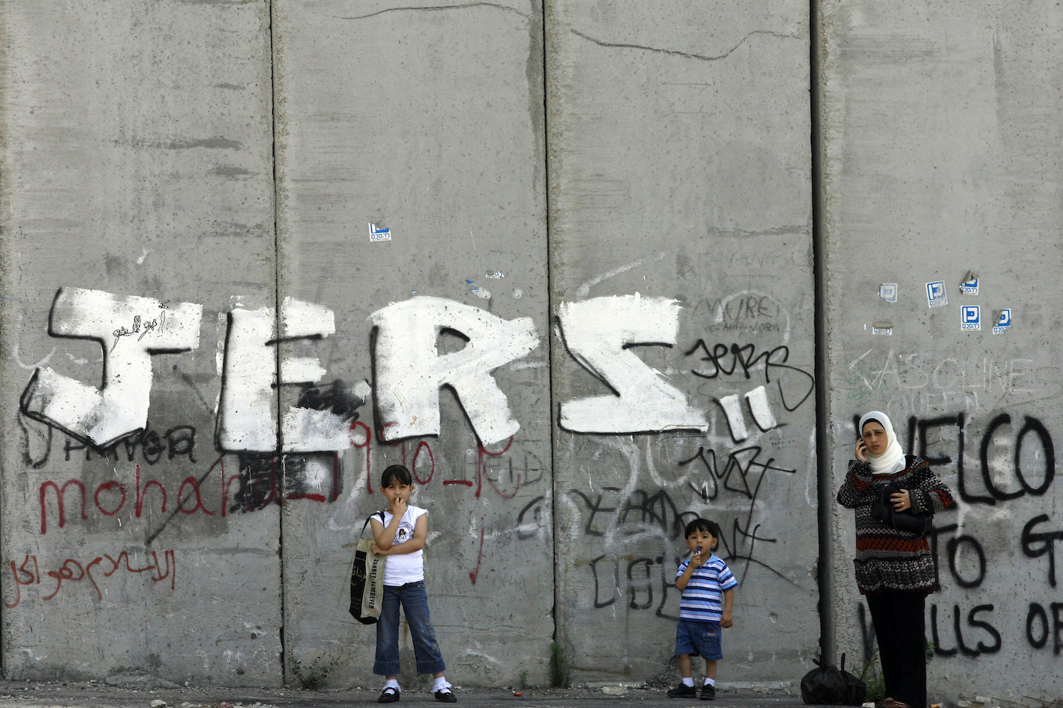 A Palestinian mother and her children stand by the separation wall in the East Jerusalem village of Abu Dis, August 08, 2008. (Michal Fattal/Flash90)