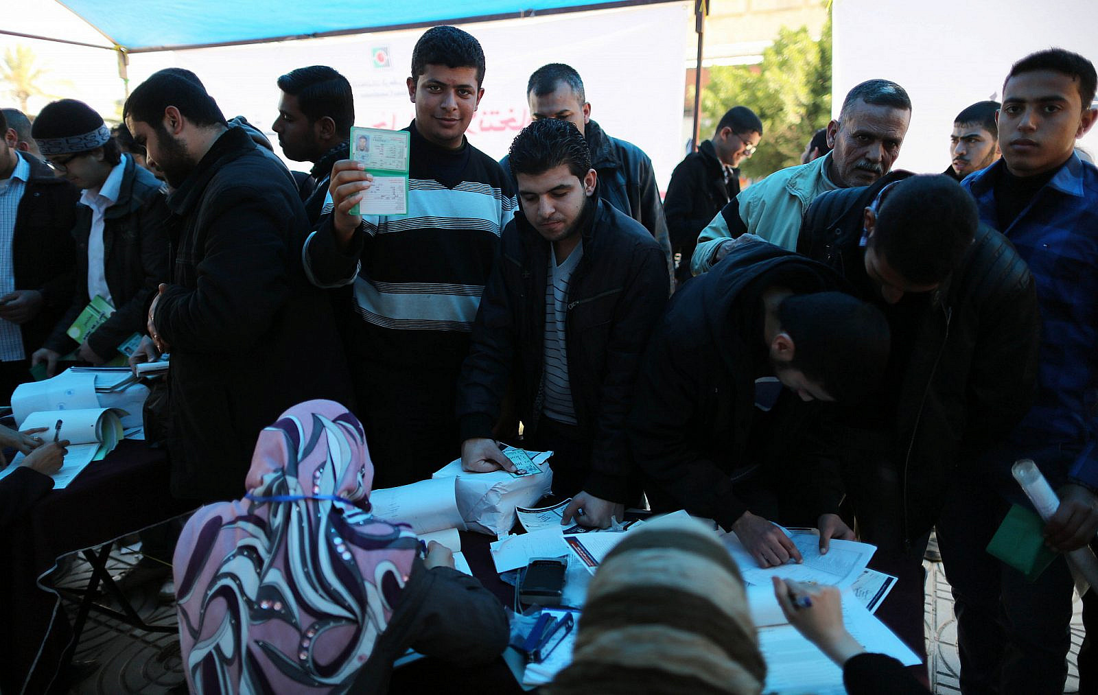 A Palestinian Central Election employee checks a voter card at a Central Election Commission office in Gaza City, February 11, 2013. (Wissam Nassar/Flash90)