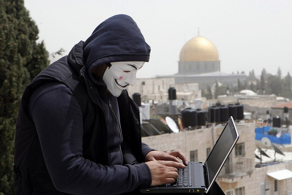 A Palestinian youth wearing a mask used by computer hackers who attacked a number of Israeli websites, seen backdropped by the Dome of the Rock, in Jerusalem's Old City. April 8 2013. (Sliman Khader/Flash90)