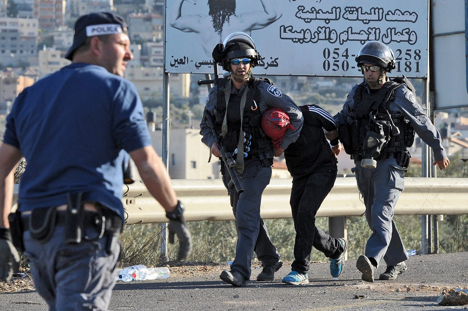 Israeli Border Police arrest Palestinian youth during clashes at the entrance to the Arab village, Kfar Kanna, in northern Israel, November 9, 2014. (Flash90)