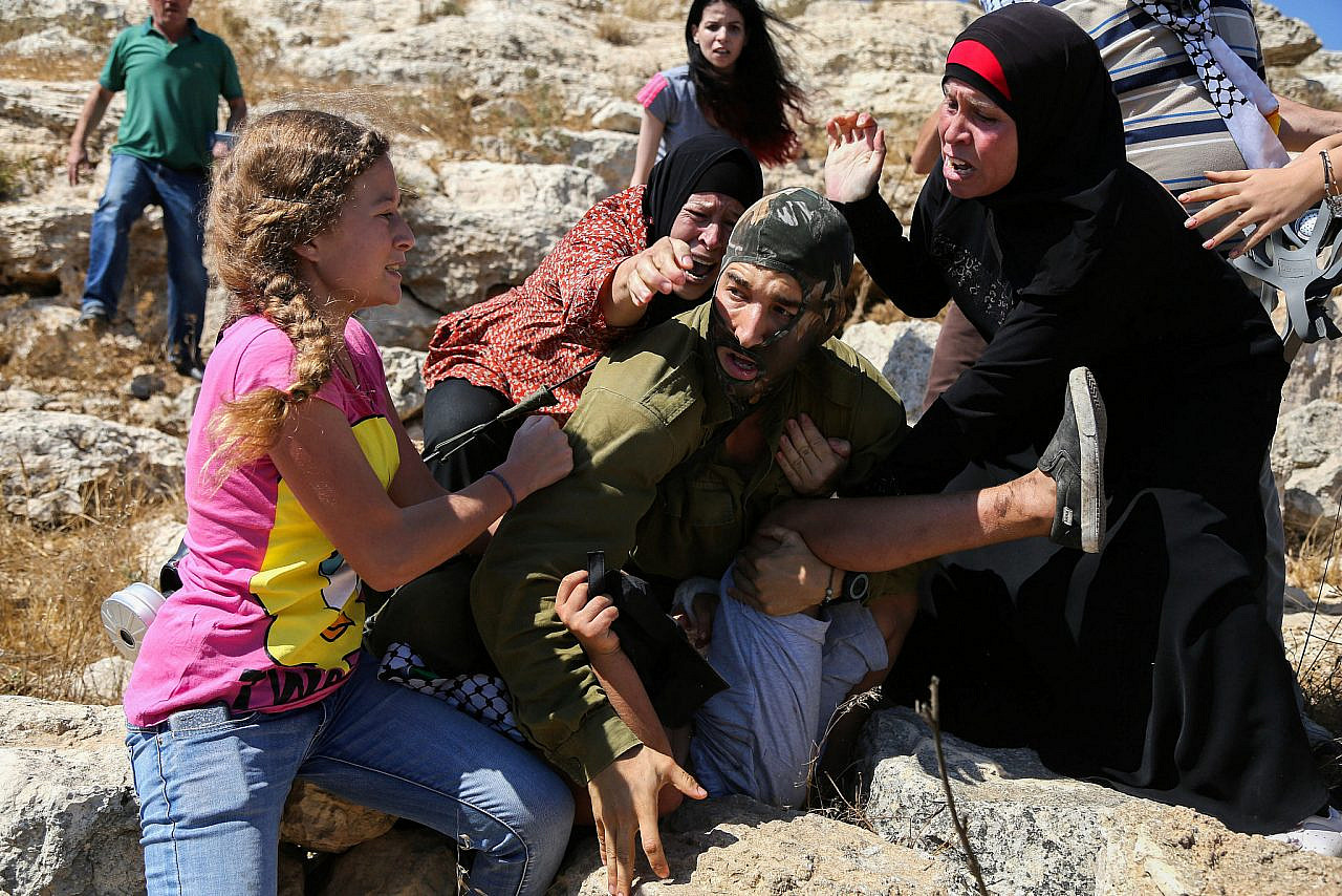 Members of the Tamimi family try to prevent an Israeli soldier from arresting Mohammed Tamimi, 12, during a protest in the village of Nabi Saleh in the occupied West Bank, August 28, 2015. (Flash90)
