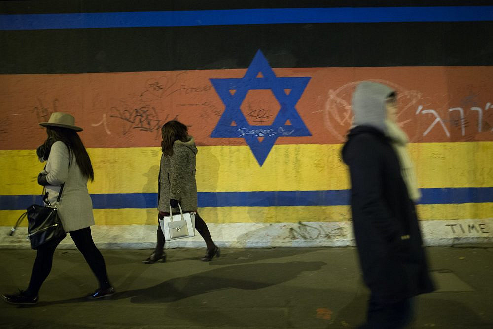 People walk by a mural depicting a combination of the Israeli and German flags on the Berlin Wall, March 13 , 2016. (Noam Revkin Fenton/Flash90)