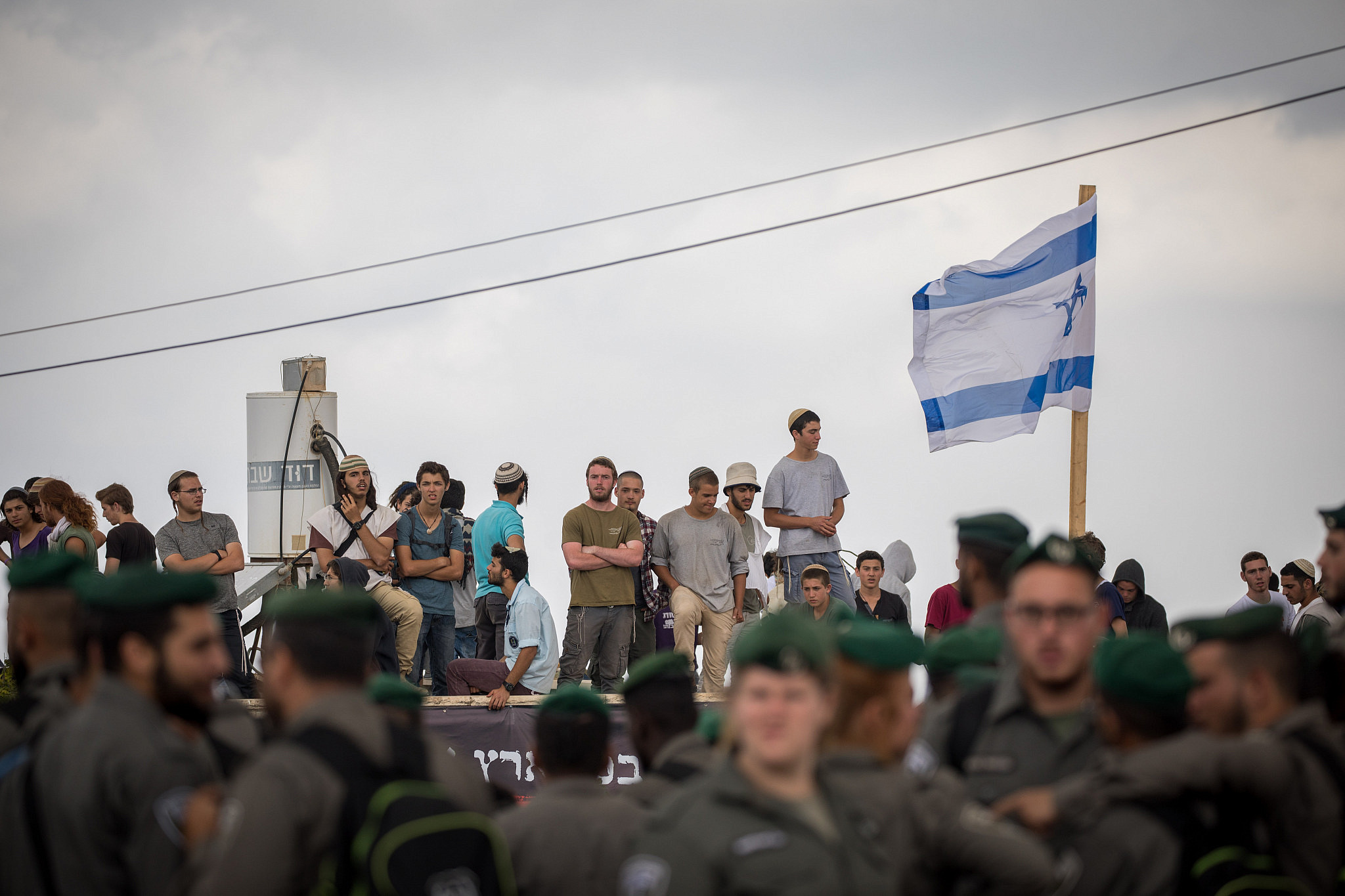 Israeli Border Police guard as settlers stand on a rooftop in the Jewish neighborhood of Netiv HaAvot in Gush Etzion, June 12, 2018. (Yonatan Sindel/Flash90)