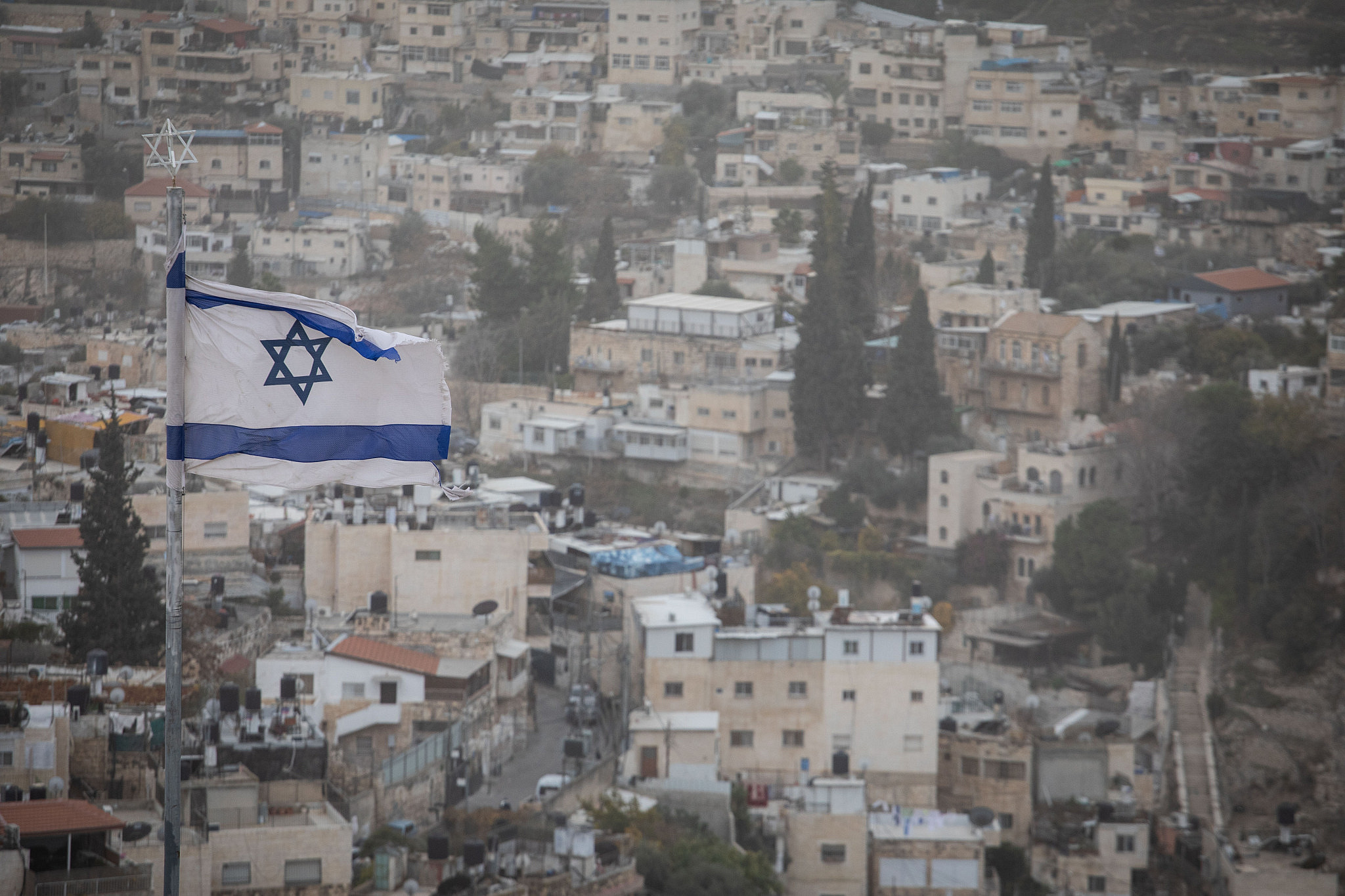 An Israeli flag over the East Jerusalem neighborhood of Silwan, seen from the Mount of Olives, December 25, 2019. (Hadas Parush/Flash90)