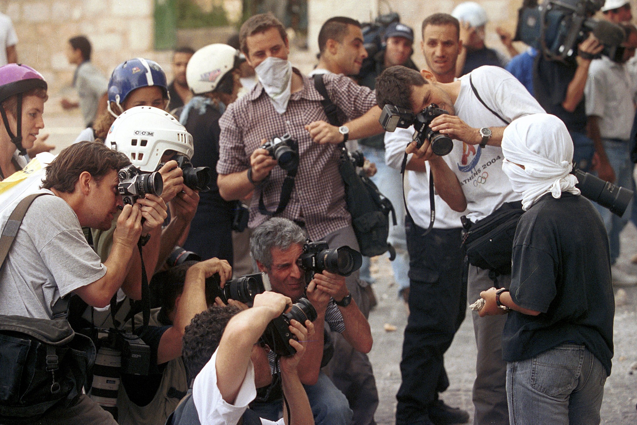 Journalists photograph a young Palestinian covering his face during clashes with Israeli police near Lions Gate in Jerusalem's Old City, October 06, 2000. Nati Shohat/Flash90