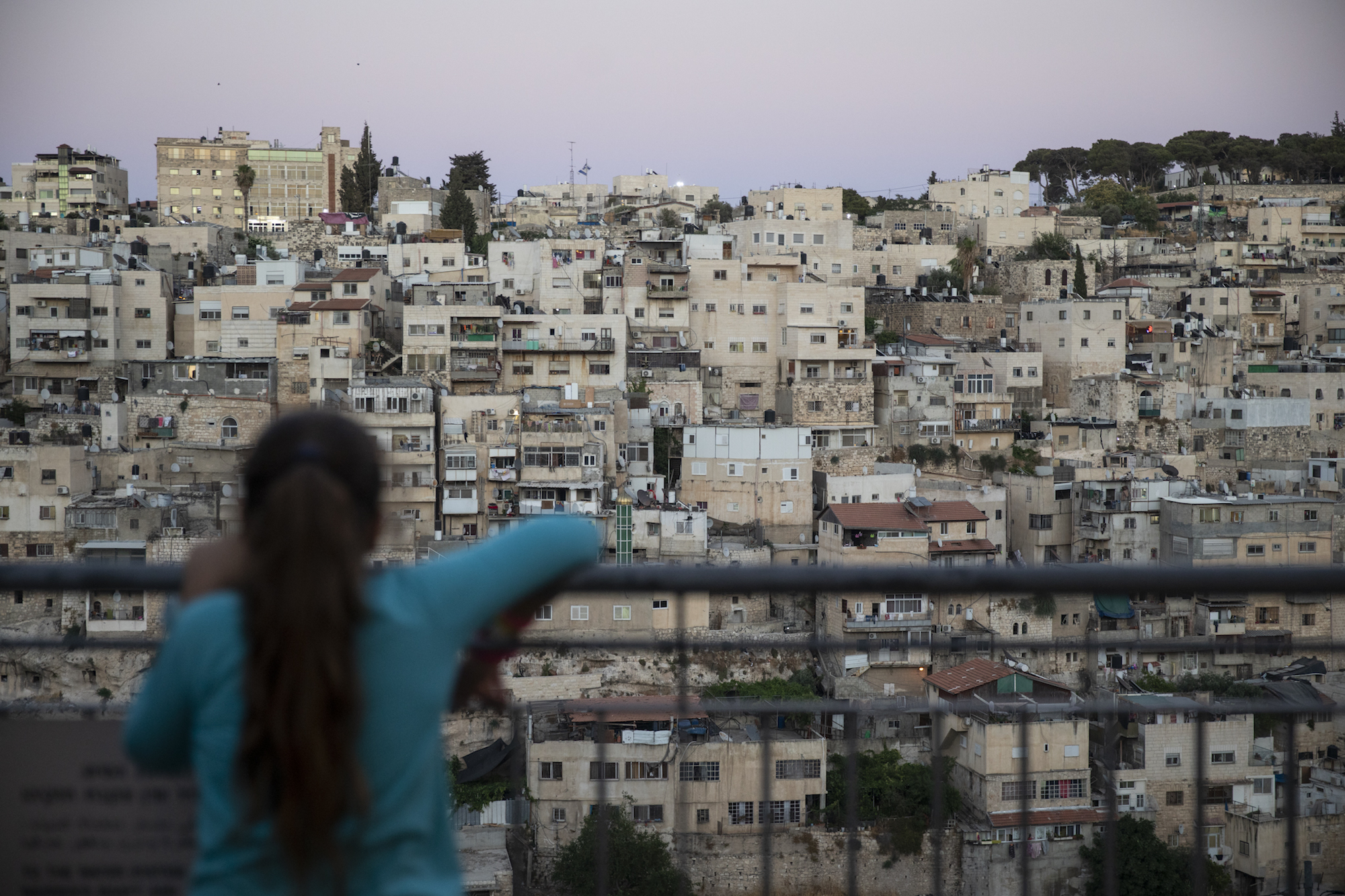 A young Jewish girl looks out from City of David National Park at the Palestinian neighborhood of Silwan, East Jerusalem, July 14, 2019. (Hadas Parush/Flash90)
