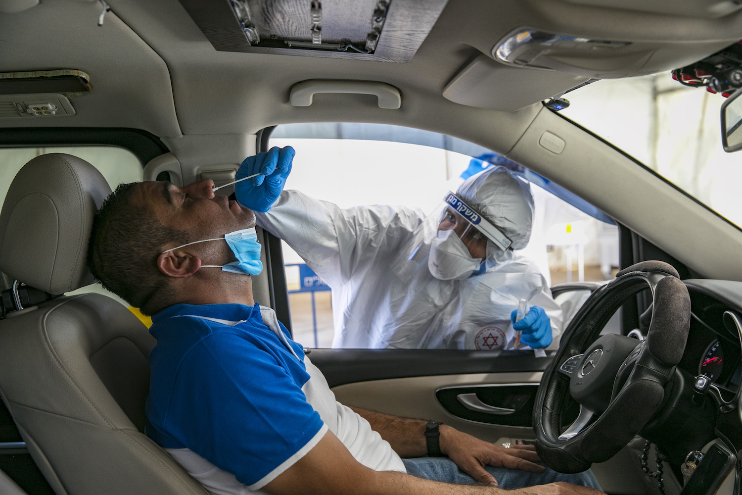 Magen David Adom medical workers perform COVID-19 tests at a drive-through site in the East Jerusalem neighborhood of Jabel Mukaber, August 18, 2020. (Olivier Fitoussi/Flash90)