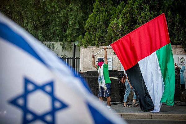 A man waves a United Arab Emirates flag outside the Prime Minister's official residence in Jerusalem, August 19, 2020. (Yonatan Sindel/Flash90)