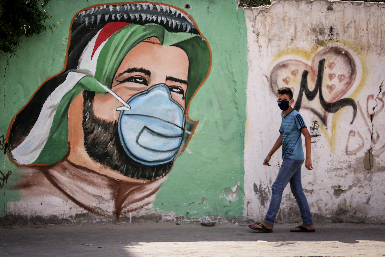 A Palestinian boy walks across a mural painted on a wall in Rafah, Gaza, as part of a campaign to raise awareness on COVID-19, on September 5, 2020. (Abed Rahim Khatib/Flash90)