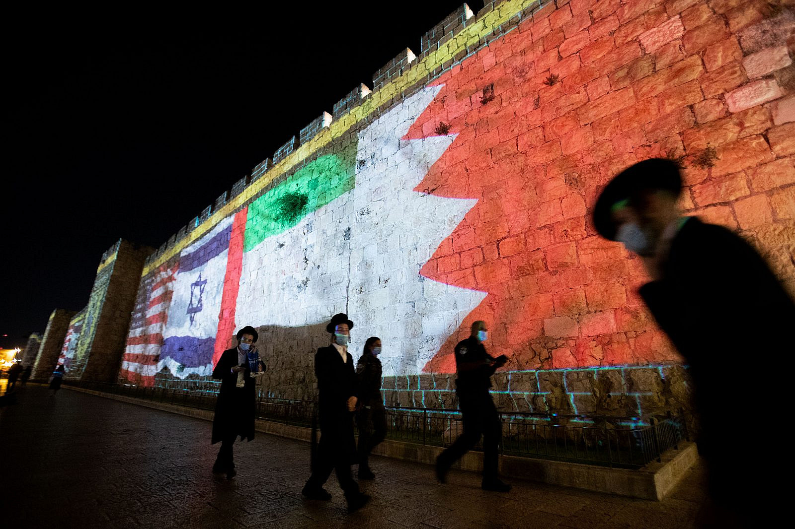 The flags of the U.S., United Arab Emirates, Israel, and Bahrain are screened on the walls of Jerusalem's Old City, September 15, 2020. (Yonatan Sindel/Flash90)
