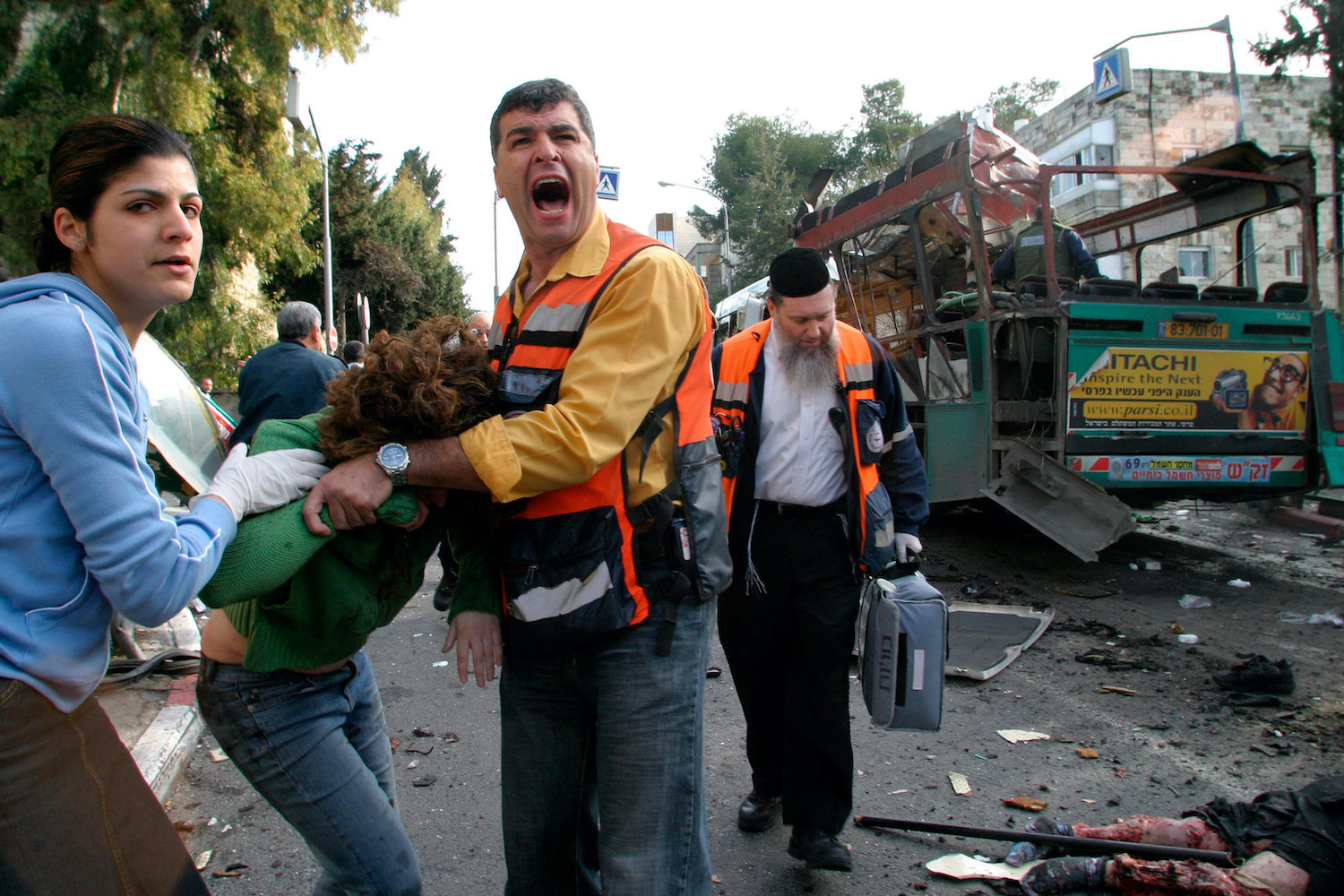 Wounded Israelis receive first aid next to the wreckage of a destroyed bus after a Palestinian suicide bomber blew himself up near Israeli Prime Minister Ariel Sharon's official residence in Jerusalem, January 29, 2004. (Haim Zach/Flash90)