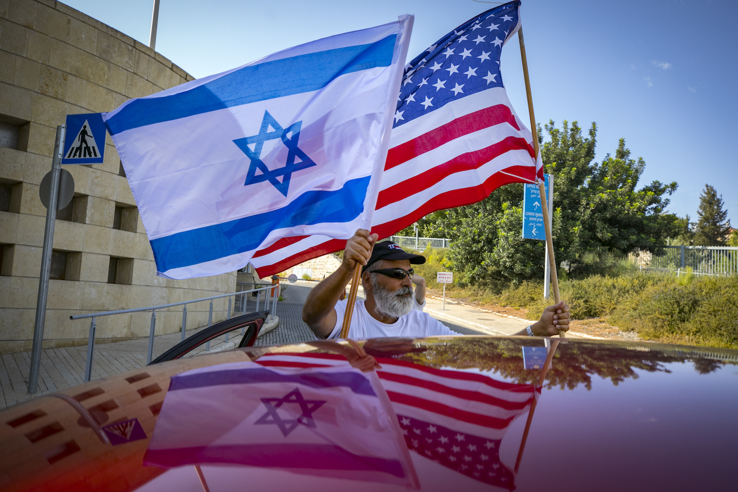 Israeli Trump supporters wave U.S. and Israeli flags outside the U.S. embassy in Jerusalem, October 27, 2020. (Olivier Fitoussi/Flash90).