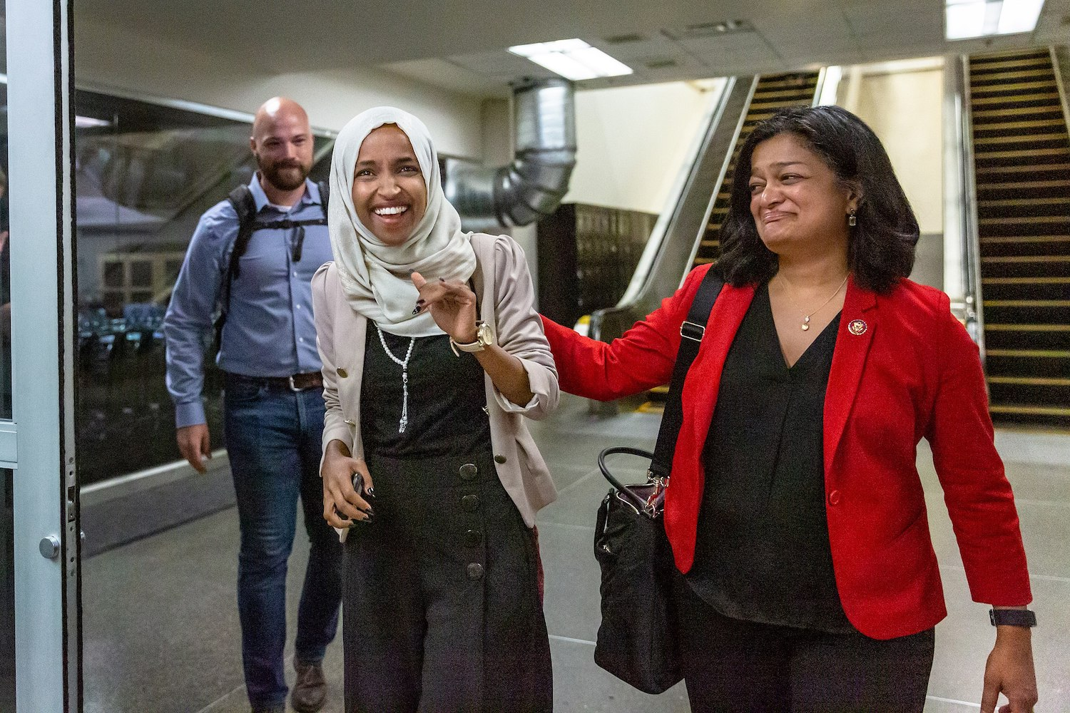 Minnesota Rep. Ilhan Omar (left) greets supporters as she lands at Minneapolis−Saint Paul International Airport, July 18. (Lorie Shaull/CC BY-SA 2.0)