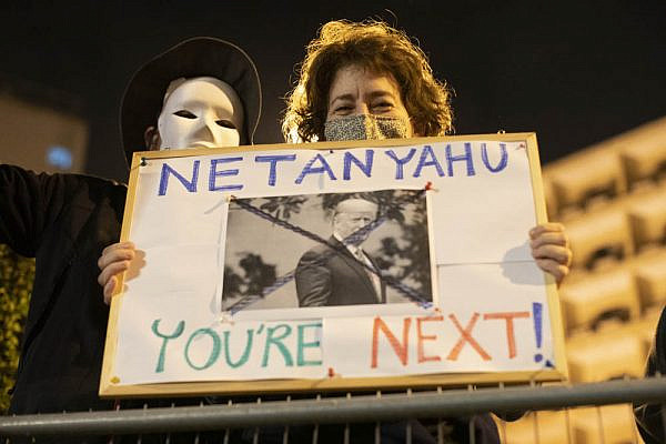 An anti-Netanyahu protester holds up a sign reading 'Netanyahu, you're next' during a demonstration against the prime minister following the election of Joe Biden to the presidency of the U.S., Jerusalem, November 7, 2020. (Oren Ziv)