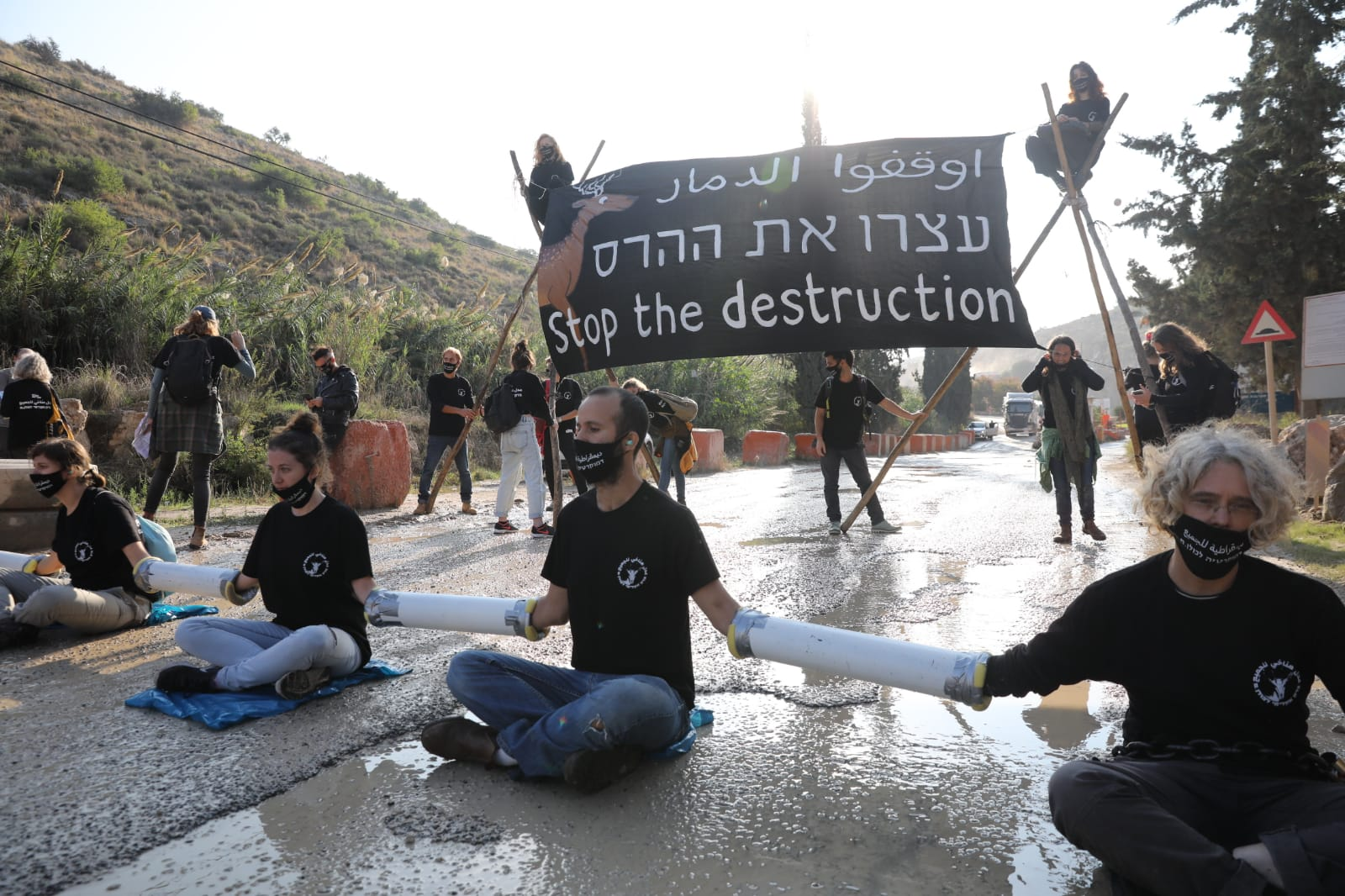Israeli climate and human rights activists chain themselves to the entrance of HeidelbergCement quarry in the occupied West Bank to protest a government plan to expand the quarry and build an industrial zone nearby, November 22, 2020. (Oren Ziv)