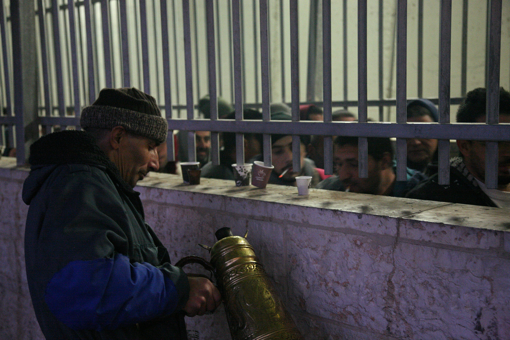 A Palestinian man sells coffee to Palestinian workers waiting to cross the Israeli Bethlehem checkpoint on their way to work, Bethlehem, West Bank, February 8, 2017. (Activestills.org)