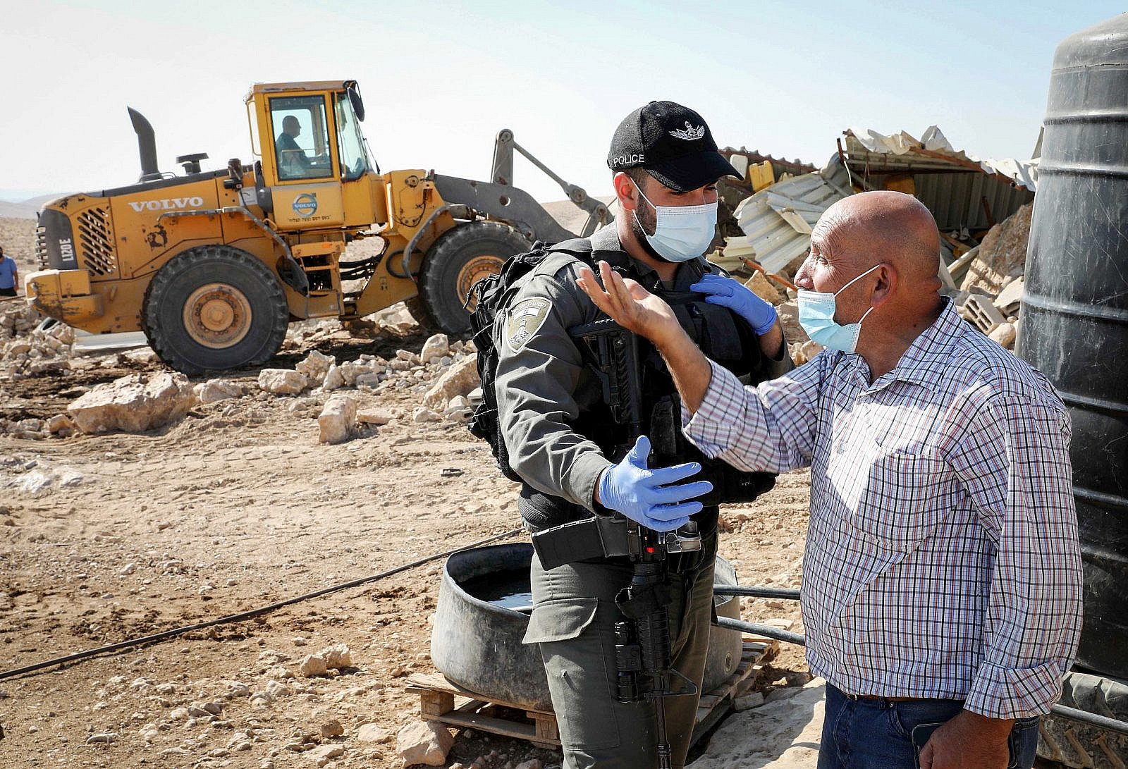 A Palestinian man argues with Israeli forces after they demolish his house and shed, near the West Bank town of Hebron, October 18, 2020. (Wisam Hashlamoun/Flash90)