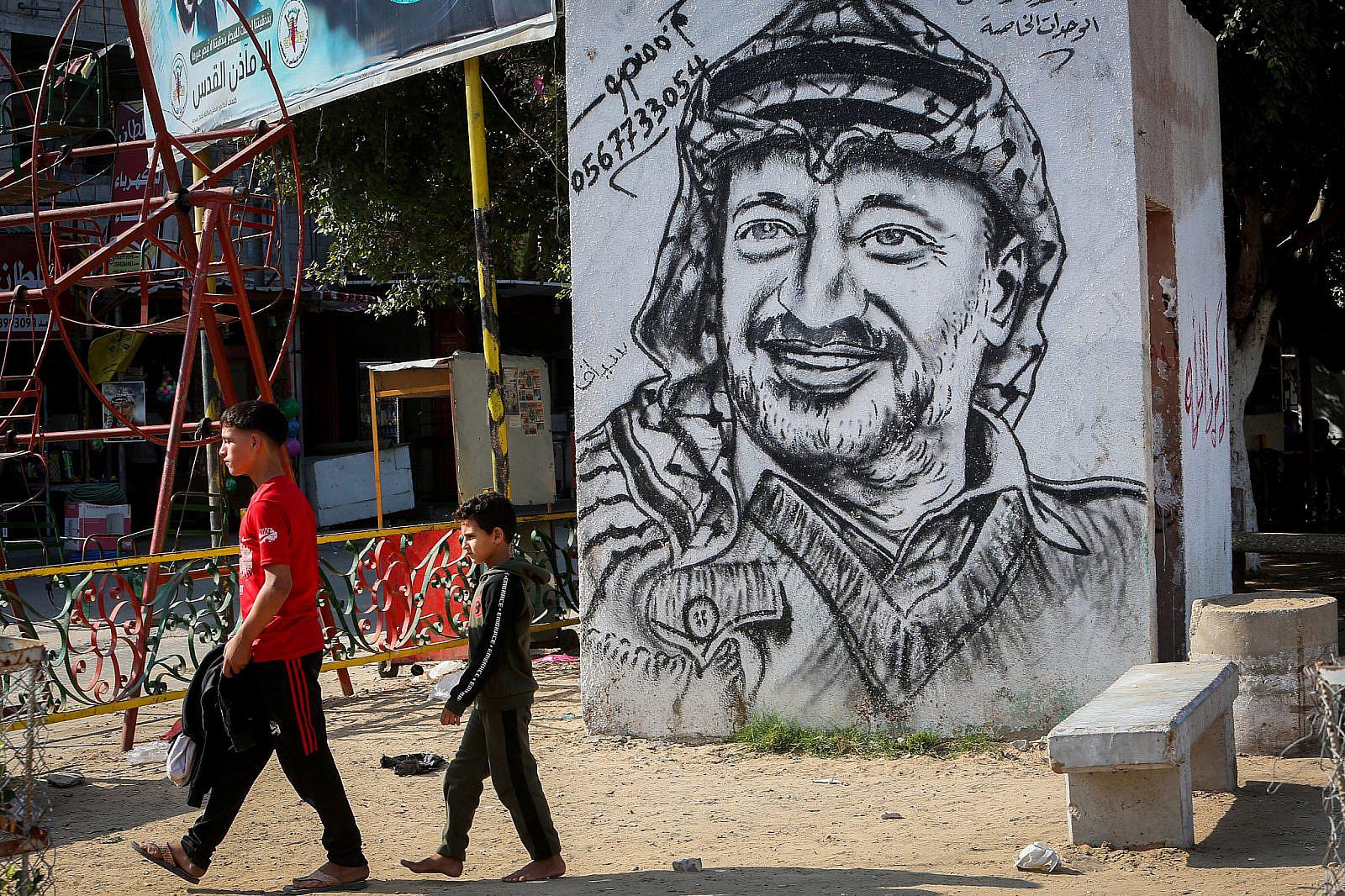 Palestinians walk near a mural depicting late Palestinian leader Yasser Arafat in Rafah, in the southern Gaza Strip, November 11, 2020. (Abed Rahim Khatib/Flash90 )