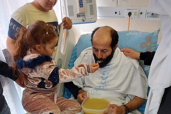 Maher al-Akhras, who after 103 days ended a hunger strike in protest at his administrative detention, is fed by his daughter at the Kaplan Medical Center, Rehovot, November 26, 2020. (Muhammad Abu As'ad Kana'na)