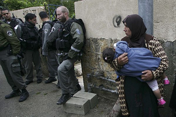 A Palestinian woman stands next to Israeli Border Police near the gate of a house in the East Jerusalem neighborhood of Sheikh Jarrah from which a Palestinian family was evicted on November 03, 2009. (Mohamar Awad/Flash90)